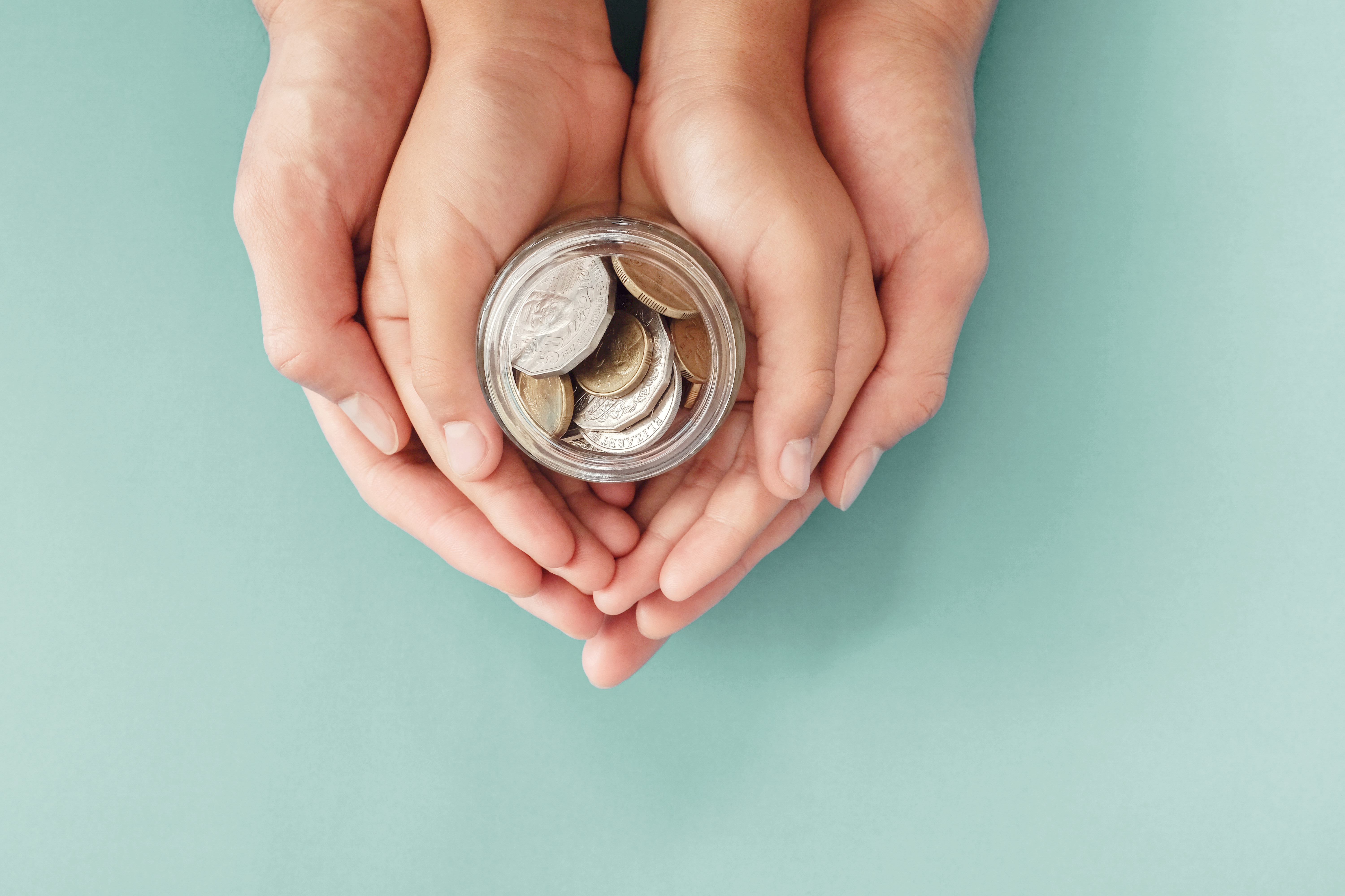 child-and-parent-hands-holding-money-jar-donation-saving-family-finance-plan-concept