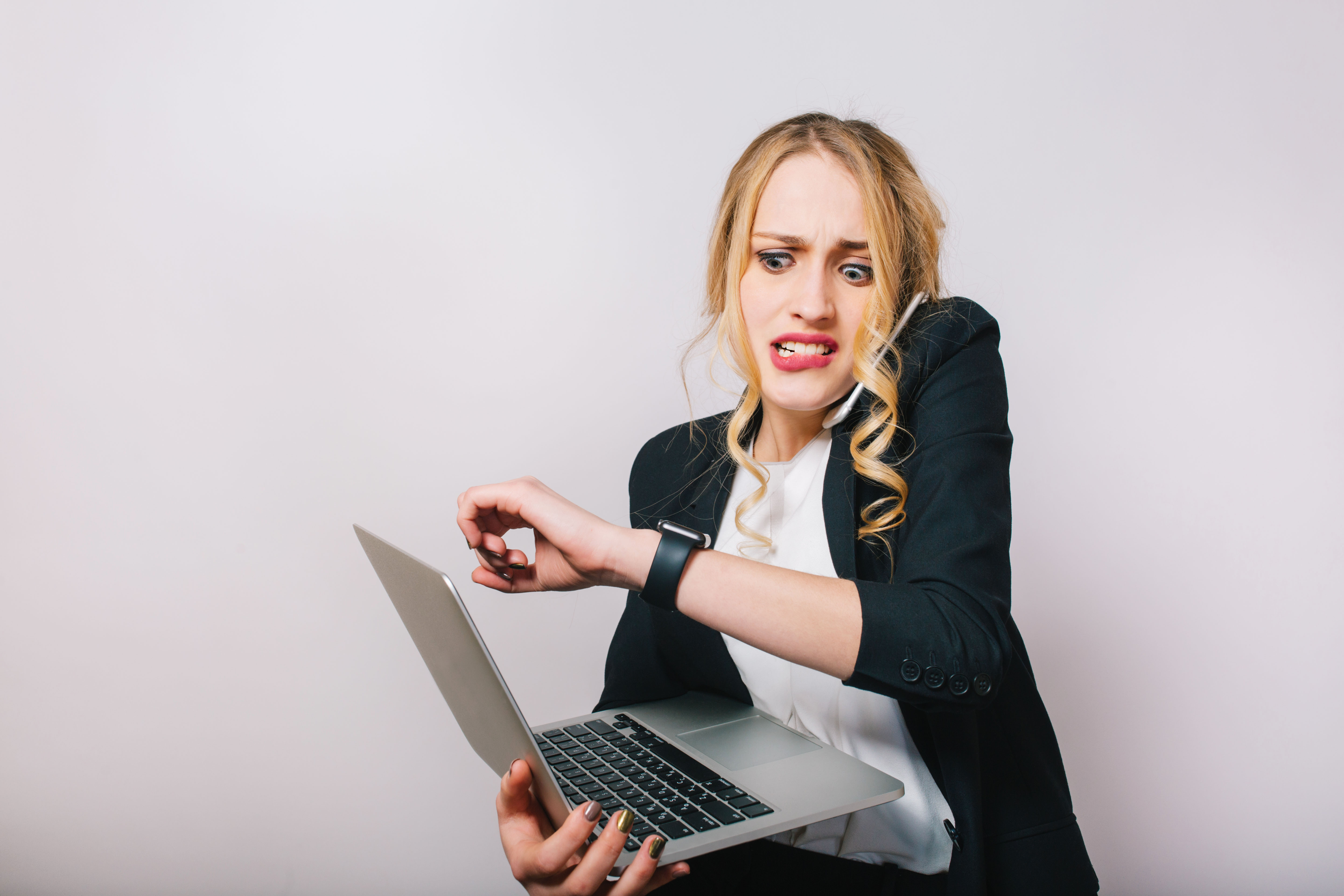 portrait-very-busy-young-businesswoman-in-formal-suit-with-laptop-talking-on-phone-looking-at-watch-being-late-job-managment-meetings-working-profession