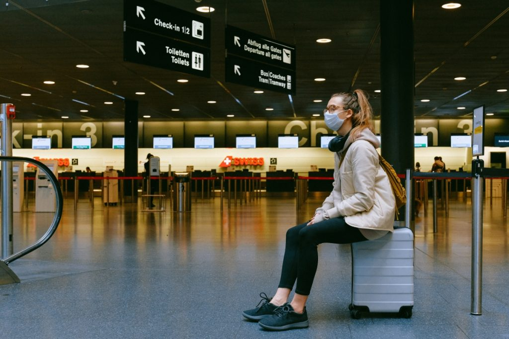girl sat on suitcase at empty airport wearing a surgical mask