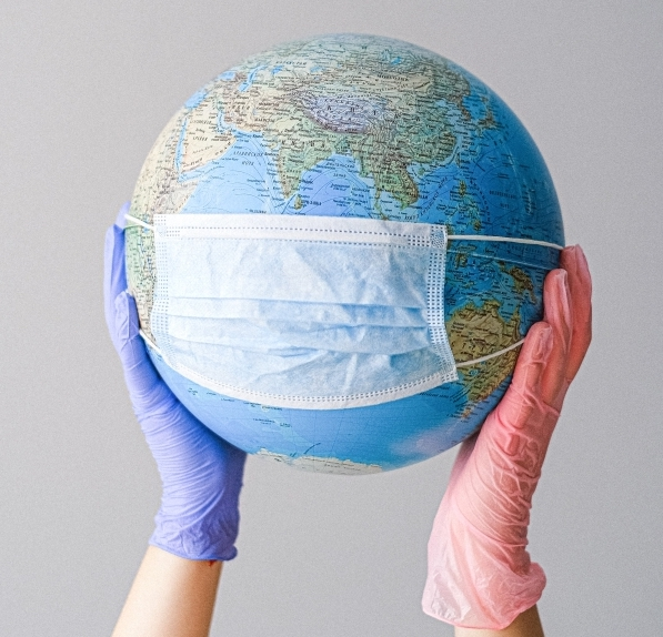 hands wearing rubber gloves holding a toy globe wearing a surgical mask